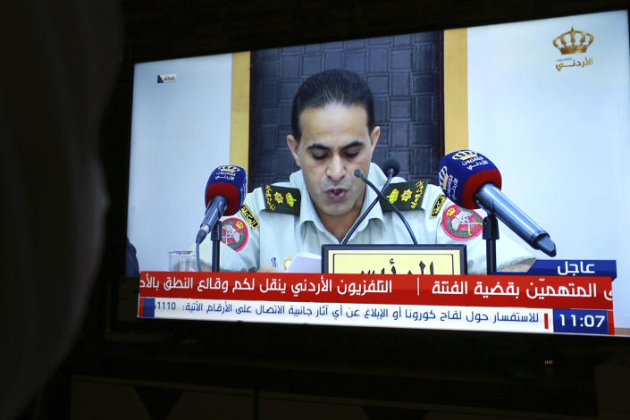 Jordan Television broadcasts Lieutenant-colonel Muwafaq al-Masaeed, military judge and president of state security court, reading the verdict in the sedition case of two former officials accused of helping Jordanian Prince Hamzah try to overthrow his half-brother King Abdullah II, in Amman, Jordan, Monday, July 12, 2021. The court sentenced the two to 15 years in prison. Bassem Awadallah, who has U.S. citizenship and once served as a top aide to King Abdullah II, and Sharif Hassan bin Zaid, a member of the royal family, were found guilty of sedition and incitement charges. (AP Photo/Raad Adayleh)