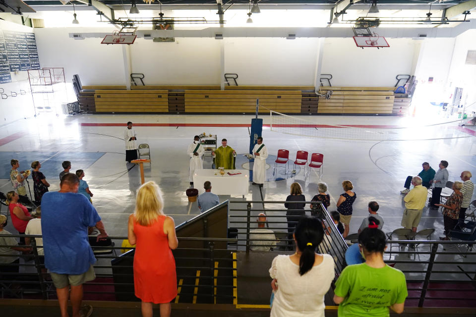 Worshipers attend a Mass led by Father David Ducote in the gymnasium at St. Joan of Arc Catholic Church in LaPlace, La., in the aftermath of Hurricane Ida, Sunday, Sept. 5, 2021. (AP Photo/Matt Slocum)