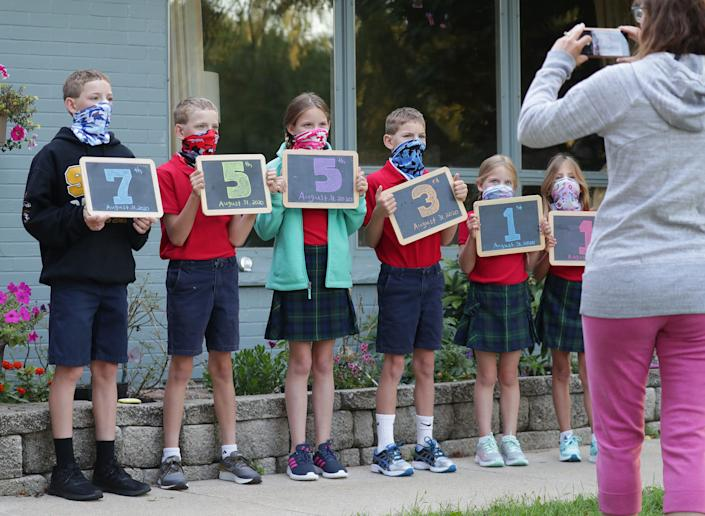 Lacey Tomczuk takes a photo of her children, all wearing masks, before they get on the bus for their first day of school in Bayside, Wis., on Aug. 31.