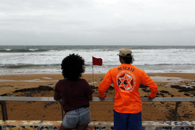 <p>A couple watch from the shore at heavy surf as hurricane Irma approaches Puerto Rico in Luquillo, on Sept. 6, 2017. (Photo: Ricardo Arduengo/AFP/Getty Images) </p>