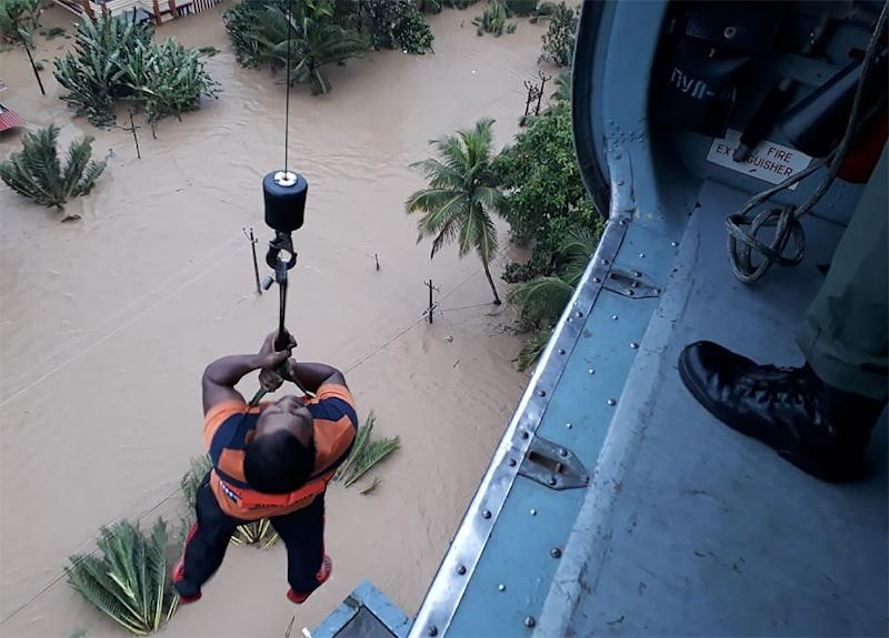 Helicopters have been battling torrential rains to reach stranded victims