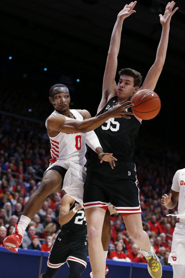 Dayton forward Zimi Nwokeji (0) passes the ball in frront of Davidson forward Luka Brajkovic (35) during the first half of an NCAA college basketball game Friday, Feb. 28, 2020, in Dayton, Ohio. (AP Photo/Gary Landers)