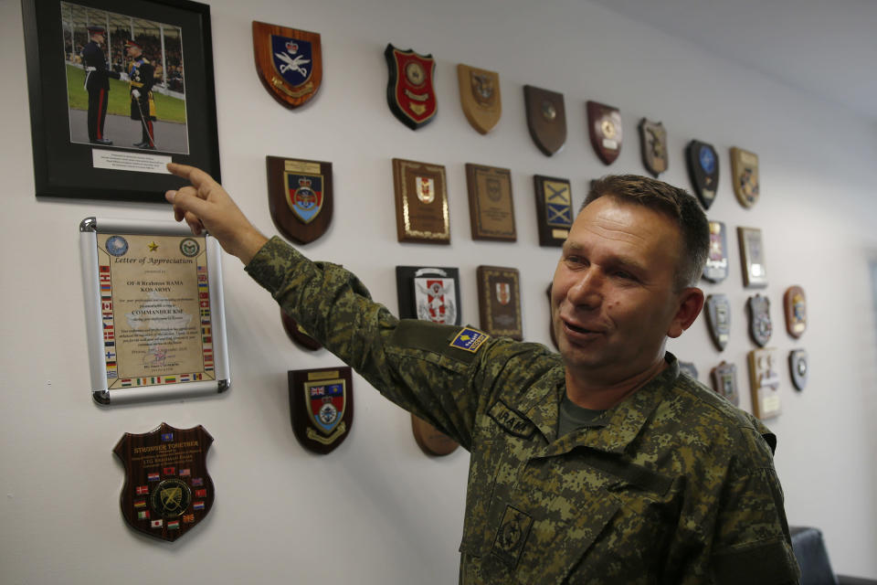 Commander of Kosovo Security Force Lt. Gen. Rrahman Rama shows a picture of KSF member Ismail Hoxha receiving a military award from Prince Charles during an interview with The Associated Press in capital Pristina, Kosovo on Thursday, Dec. 13, 2018, a day before the parliament votes to transform Kosovo Security Force into a regular army. Kosovo lawmakers are set to transform the Kosovo Security Force into a regular army, a move that significantly heightened tension with neighboring Serbia which even left open a possibility of an armed intervention in its former province. (AP Photo/Visar Kryeziu)