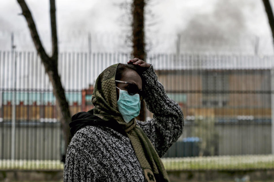 A woman wearing a mask walks out of the Rebibbia prison as smoke billows following inmates' protests, in Rome, Monday, March 9, 2020. Italian penitentiary police say six inmates protesting coronavirus containment measures at the northern Italian prison of Modena have died after they broke into the infirmary and overdosed on methadone. The protest Sunday in Modena was among the first of more than two-dozen riots at Italy's overcrowded lock-ups that grew Monday. (Cecilia Fabiano/LaPresse via AP)