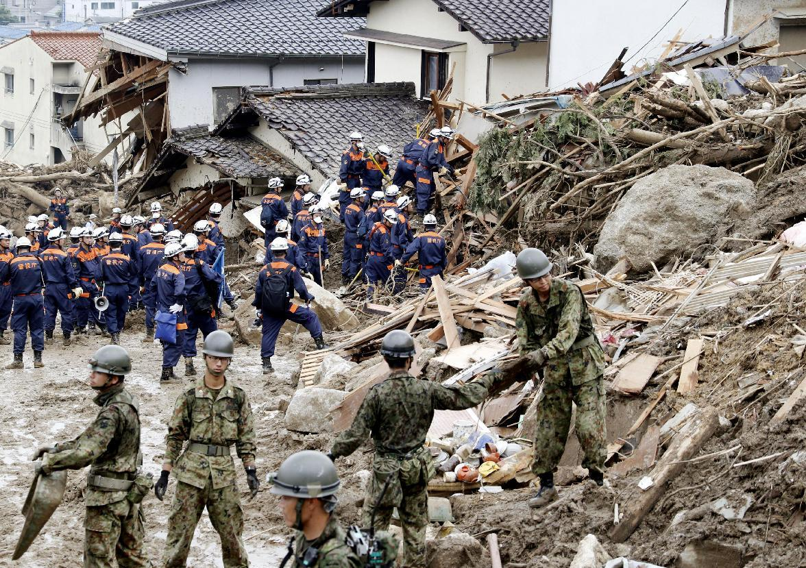 Firefighters and Self-Defense Force members make search operation for the people still missing in a mud-covered residential area following a massive landslide in Hiroshima, western Japan, Sunday, Aug. 24, 2014. Dozens of people were dead after torrents of mud, rocks and timber swept through at least five valleys in Hiroshima's suburbs after heavy rains early Wednesday. About 2,800 police and military personnel have been searching for the victims, at times suspending their work to reduce risks from further slides. (AP Photo/Kyodo News) JAPAN OUT