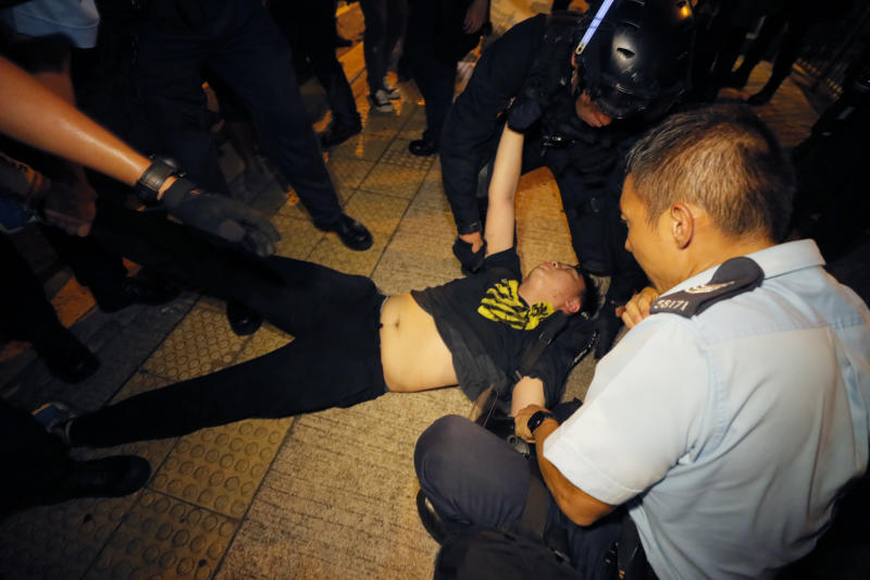 Hong Kong police officers hold down a protester at a rally against the proposed amendments to the extradition law at the Legislative Council in Hong Kong during the early hours of Monday, June 10, 2019. The extradition law has aroused concerns that this legislation would undermine the city's independent judicial system as it allows Hong Kong to hand over fugitives to the jurisdictions that the city doesn't currently have an extradition agreement with, including mainland China, where a fair trial might not be guaranteed. (AP Photo/Kin Cheung)