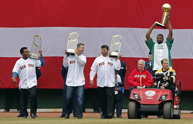 Former Boston Mayor Tom Menino, seated left, drives in from left field with former Boston Bruins' Mark Recchi, seated right, former Boston Celtics' Leon Powe, standing right, and former Red Sox players from left, Pedro Martinez, Mike Lowell and Jason Varitek during pre-game ceremonies before a baseball game against the Milwaukee Brewers on Opening Day at Fenway Park in Boston, Friday, April 4, 2014. (AP Photo/Michael Dwyer)