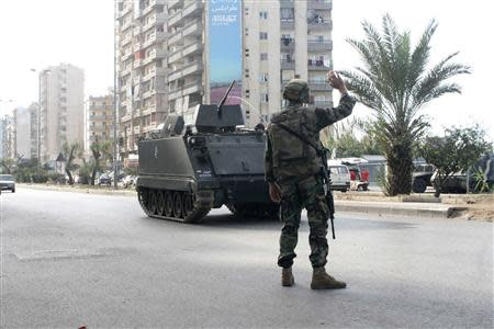 A Lebanese army soldier gestures to an armoured vehicle in Tripoli, northern Lebanon, November 30, 2013. REUTERS/Stringer