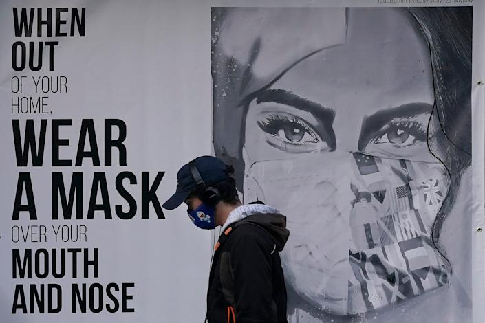 A pedestrian walks past a mural in San Francisco, which is joining a statewide curfew and Silicon Valley is banning all high school, collegiate and professional sports and imposing a quarantine for those traveling into the region from more than 150 miles away.