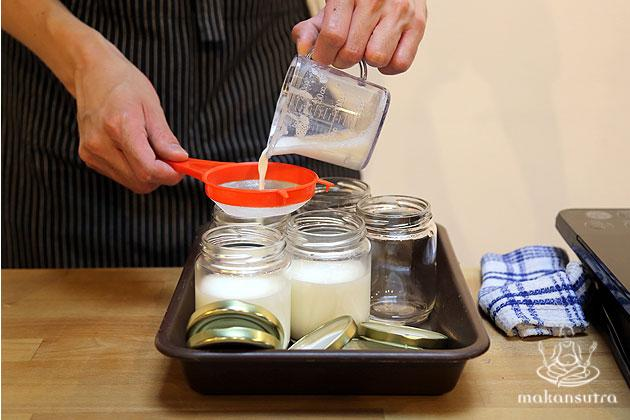 Pour the yoghurt milk into clean glass jars. Use a strainer for smoother consistency.