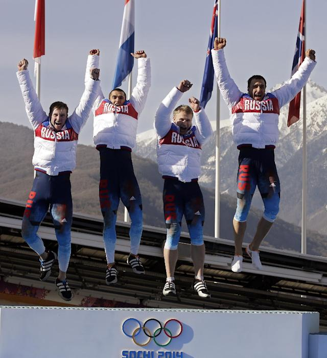 The team from Russia RUS-1, with Alexander Zubkov, Alexey Negodaylo, Dmitry Trunenkov, and Alexey Voevoda, jump onto the medal stand after they won the gold medal during the men's four-man bobsled competition final at the 2014 Winter Olympics, Sunday, Feb. 23, 2014, in Krasnaya Polyana, Russia. (AP Photo/Michael Sohn)