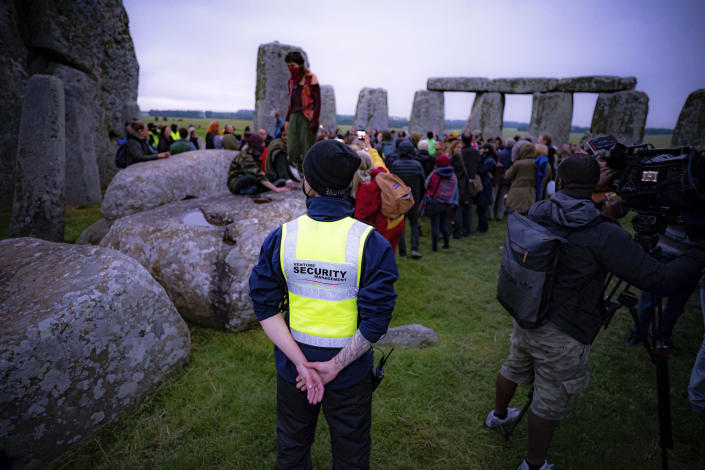 Security keep watch as people stand inside the stone circle during Summer Solstice at Stonehenge, where some people jumped over the fence to enter the stone-circle to watch the sun rise at dawn of the longest day of the year in the UK, in Amesbury, England, Monday June 21, 2021. The prehistoric monument of ancient stones have been officially closed for the celebrations due to the coronavirus lockdown, but groups of people ignored the lockdown to mark the Solstice, watched by low key security. (Ben Birchall/PA via AP)