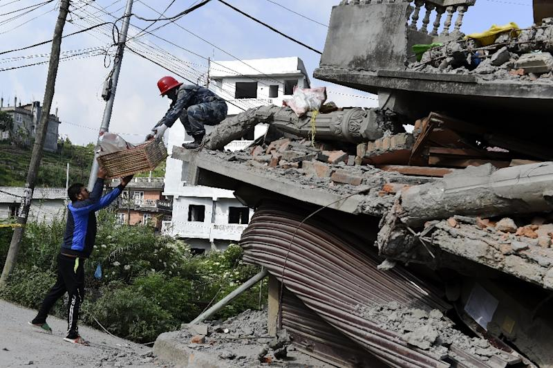 A Nepalese rescue personnel (R) hands belongings found inside an apartment building which collapsed under its own weight after an earthquake to a resident in Kathmandu on May 14, 2015 (AFP Photo/Roberto Schmidt)