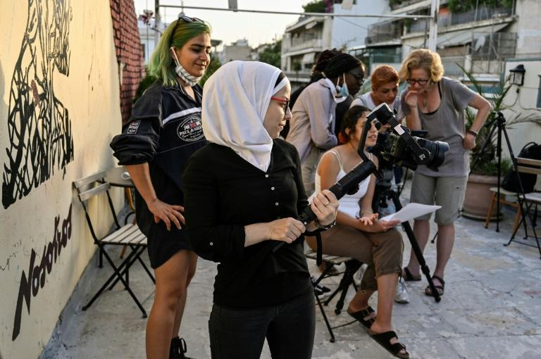 Ataa Bremo from Syria and other refugees film an interview on gender-based violence