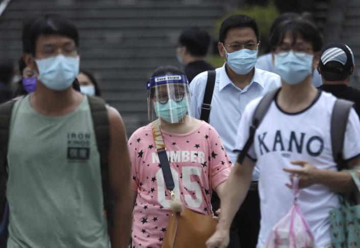 People wearing face masks to protect against the spread of the coronavirus walk in the light rain from approaching Typhoon In-Fa in Taipei, Taiwan, Thursday, July 22, 2021. (AP Photo/Chiang Ying-ying)