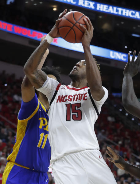 North Carolina State's Manny Bates (15) drives to the basket as Pittsburgh's Justin Champagnie (11) defends during the first half of an NCAA college basketball game at PNC Arena in Raleigh, N.C., Saturday, Feb. 29, 2020. (Ethan Hyman/The News & Observer via AP)