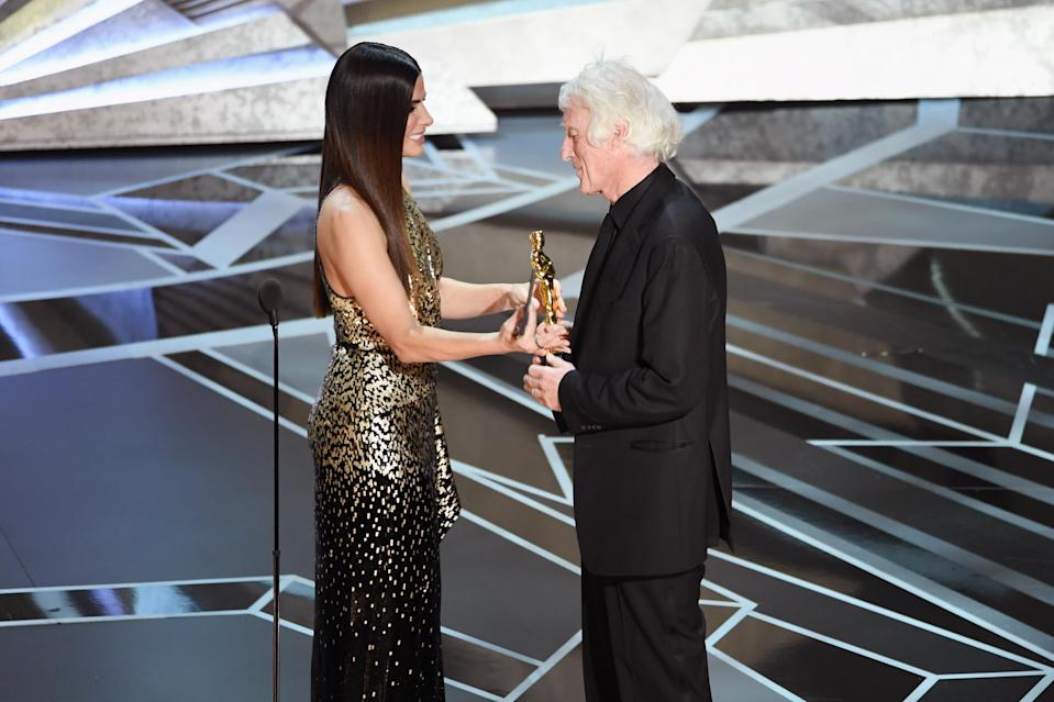 HOLLYWOOD, CA – MARCH 04: Cinematographer Roger A. Deakins (R) accepts Best Cinematography for 'Blade Runner 2049' from actor Sandra Bullock onstage during the 90th Annual Academy Awards at the Dolby Theatre at Hollywood & Highland Center on March 4, 2018 in Hollywood, California. (Photo by Kevin Winter/Getty Images)