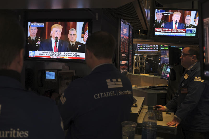 FILE - In this Jan. 8, 2020, file photo traders pause to watch a televised speech by President Donald Trump as they work the floor of the New York Stock Exchange in New York. A potentially tumultuous presidential election campaign promises to add some extra drama to financial markets this year, although if history is any guide investors can cast aside some worries. (AP Photo/Seth Wenig, File)