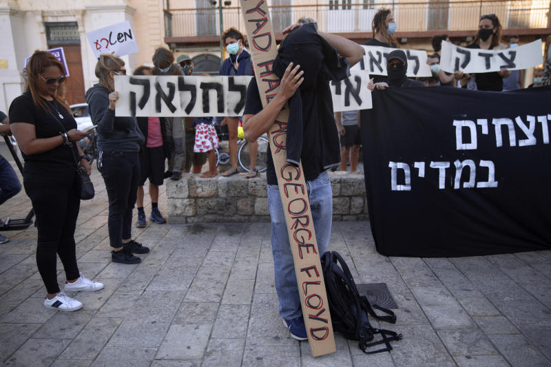 """Protesters hold signs during a demonstration against the Israeli police after border police officers shot and killed Iyad al-Halak, an unarmed autistic Palestinian man, in the mixed Arab Jewish city of Jaffa, near Tel Aviv, Israel, after saying they suspected he was carrying a weapon, Sunday, May 31, 2020. Protesters gathered to protest the killing of al-Halak in Jerusalem and the killing of George Floyd in Minneapolis last week. Hebrew sign reads, """"Murderers in uniform."""" (AP Photo/Oded Balilty)"""