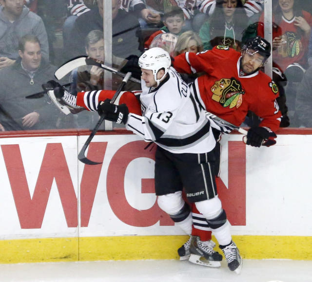 Los Angeles Kings left wing Kyle Clifford (13) checks Chicago Blackhawks defenseman Michal Rozsival along the boards during the first period of an NHL hockey game Monday, Dec. 30, 2013, in Chicago. (AP Photo/Charles Rex Arbogast)