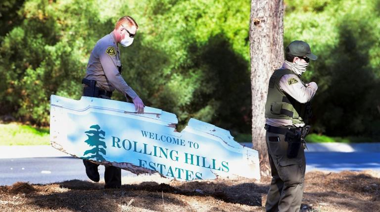 Police carry a sign broken in Woods' crash