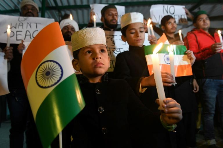Young demonstrators hold placards and candles during a protestagainst India's new citizenship law at a mosque in Amritsar