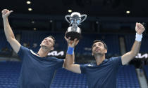 Croatia's Ivan Dodig, right, and Slovakia's Filip Polasek hold their trophy aloft after defeating Rajeev Ram of the US and Britain's Joe Salisbury in the men's doubles final at the Australian Open tennis championship in Melbourne, Australia, Sunday, Feb. 21, 2021.(AP Photo/Andy Brownbill)