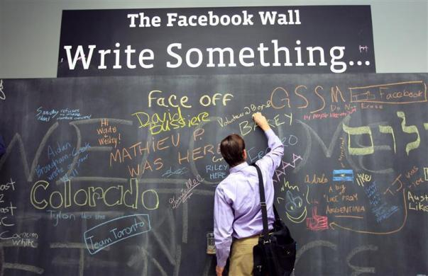 An employee writes a note on the message board at the new headquarters of Facebook in Menlo Park, California January 11, 2012.