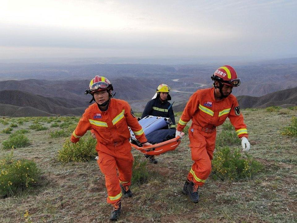Rescue workers carry a stretcher as they work to rescue participants in Baiyin race. Photo: Reuters