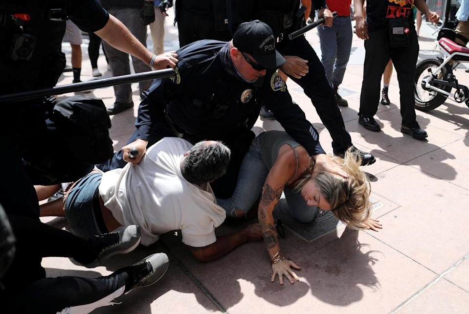 <p>A police officer pins a woman down during confrontations with protesters in Huntington Beach</p> (REUTERS)