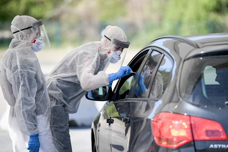 23 April 2020, Berlin: Employees from the Health Department in Mitte hold a swab in a car window on the central fairground in the outpatient corona test facility. The car can now be driven through the Drive-Inn to get a medical smear. For this purpose, the Health Office in Mitte allocates individual time windows by telephone. The tests are to be evaluated by the state laboratory within 24 hours. Photo: Britta Pedersen/dpa-Zentralbild/ZB (Photo by Britta Pedersen/picture alliance via Getty Images)