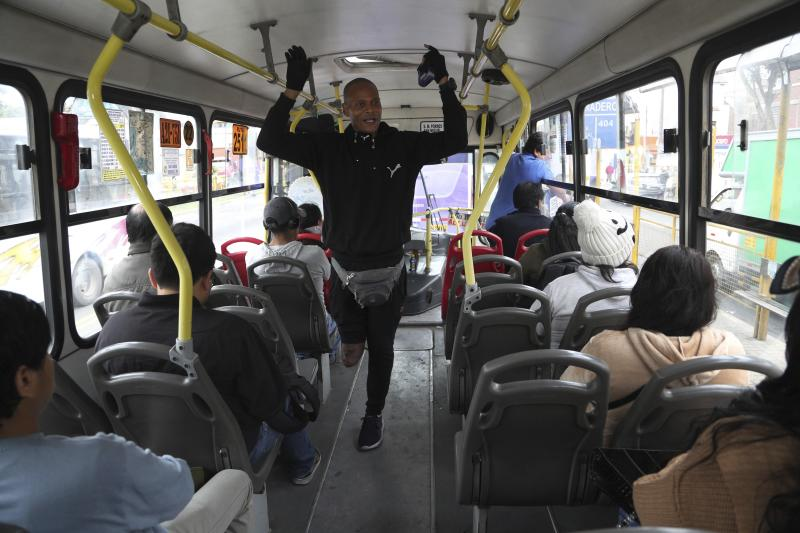 In this Oct. 8, 201 photo, Venezuelan migrant Freddy Brito, who lost a leg when he was shot years ago at a party in Venezuela, sings for tips in a public bus in Lima, Peru. Once part of a popular merengue house band, Brito said his family worried about their security in a country where robberies and kidnappings are frequent. (AP Photo/Martin Mejia)