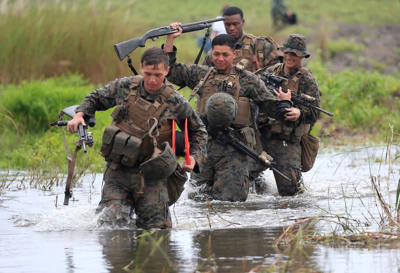 FILE PHOTO: U.S. military forces cross a flooded area near the shore during the annual Philippines-US amphibious landing exercise (PHIBLEX) at San Antonio