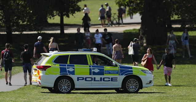 Police officers in a patrol car keep people moving in Greenwich Park, London. (PA)