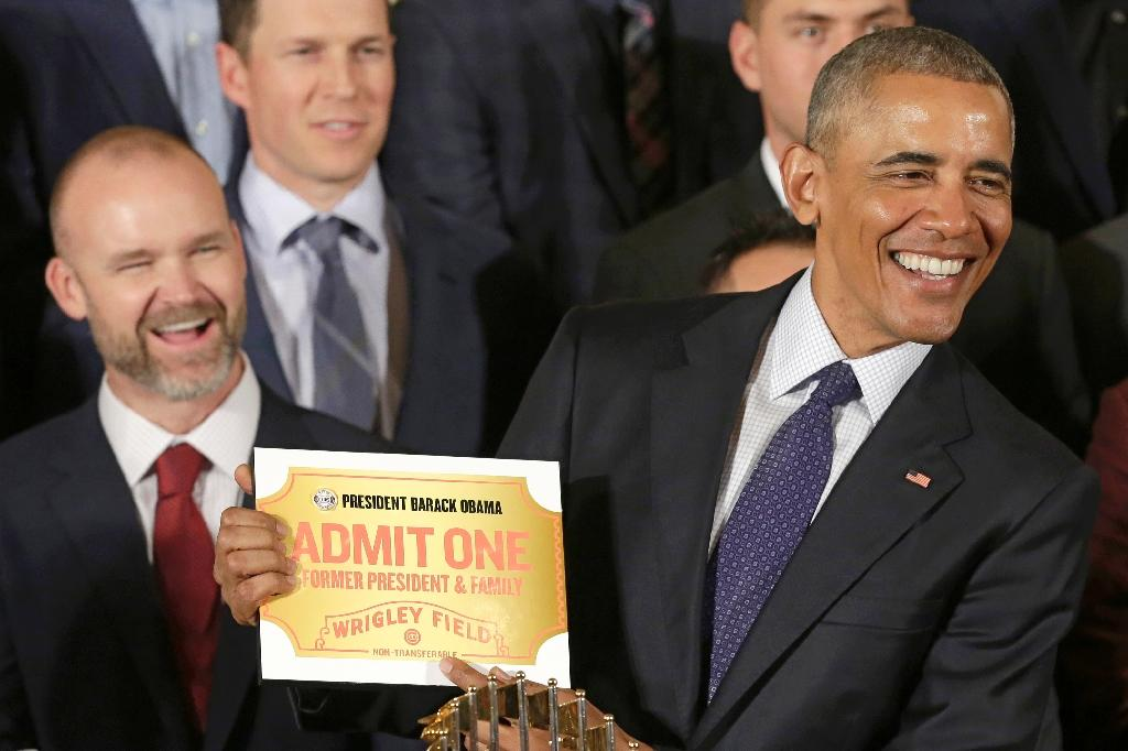 US President Barack Obama holds a lifetime admission certificate as he welcomes the Chicago Cubs baseball team to the White House on January 16, 2017 (AFP Photo/YURI GRIPAS)