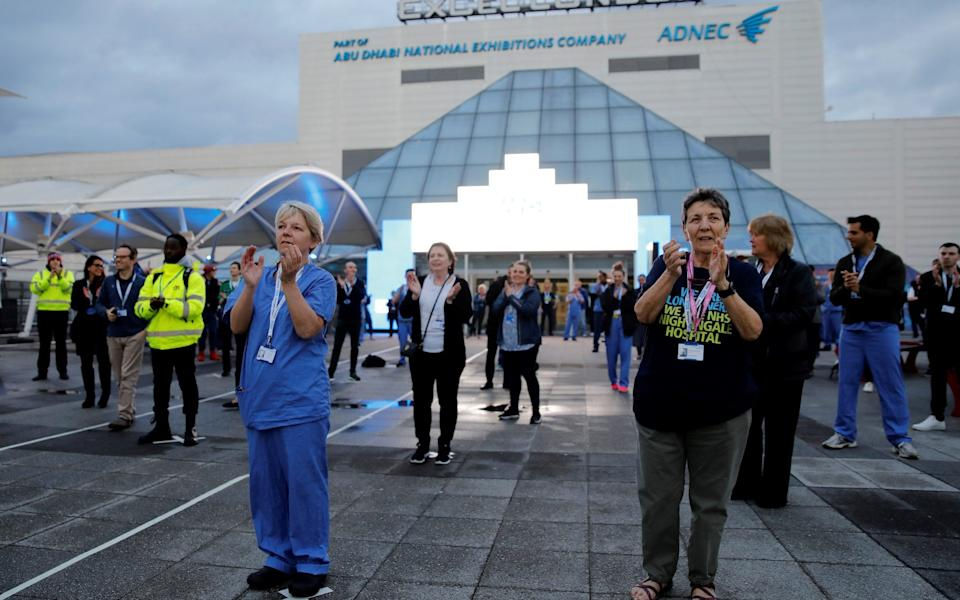 "Medical staff and workers take part in a national ""clap for carers"" outside the ExCeL London exhibition centre, which was transformed into the NHS Nightingale field hospital in London - Tolga Akmen/Getty Images"