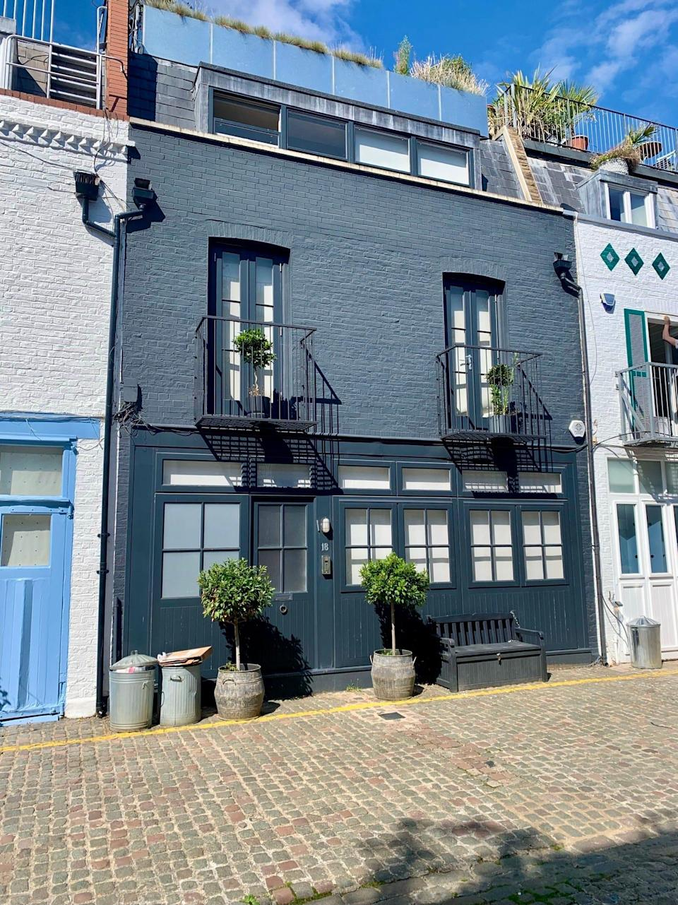 Number 18 St. Lukes Mews is a darker grey and has neat plant pots outside.