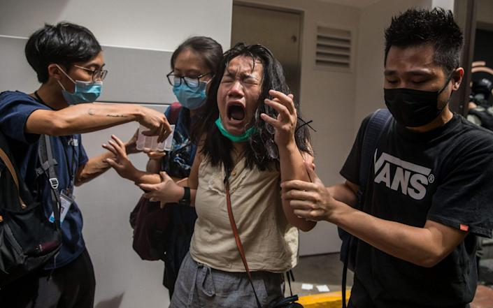 A woman reacts after being hit with pepper spray - DALE DE LA REY/AFP via Getty Images
