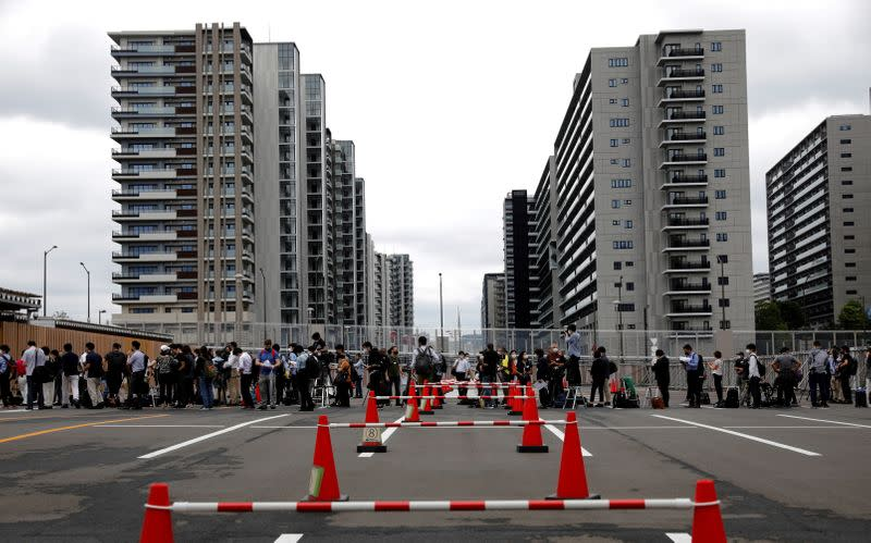 Journalists stand in a line to enter the village plaza of the Tokyo 2020 Olympic and Paralympic Village for a press tour in Tokyo