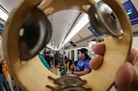 A supporter of Mexico's Tigres holds a tambourine while riding with other fans in the Doha Metro on the way to a club fan event outside Education City Stadium in the Qatari city of Ar-Rayyan