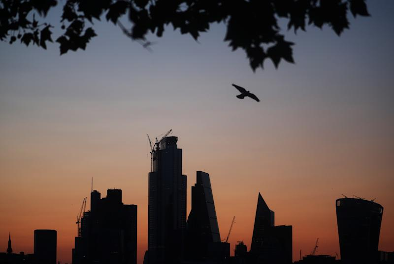 A bird flies as the sun rises behind the city of London financial district in London, Britain August 20, 2019. REUTERS/Hannah McKay