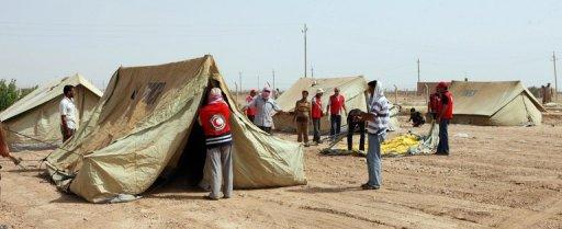 "Red Crescent personnel set up tents in the Iraqi town of al-Qaim near the border with Syria for refugees fleeing the fighting in Syria. Having fled a city where shells fell ""like rain"" and children died in front of them, Syrian refugees spoke of the hell that would erupt every night as troops sought to retake their border town"