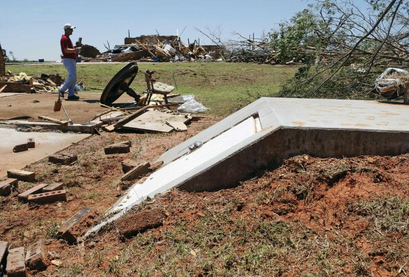 In this May 26, 2011 photo, Randy Matthews, background, carries a piece of tornado debris in Piedmont, Okla., past the door of the tornado shelter where his mother, Betty Matthews, not pictured, stayed in safely during Tuesday's deadly tornado. The old-fashioned storm shelters that once dotted yards across the Plains have become relics of the past as home buyers invest in other features, like extra rooms, or try to save money. But violent weather is prompting some homeowners to give the shelters a second look. (AP Photo/Sue Ogrocki)