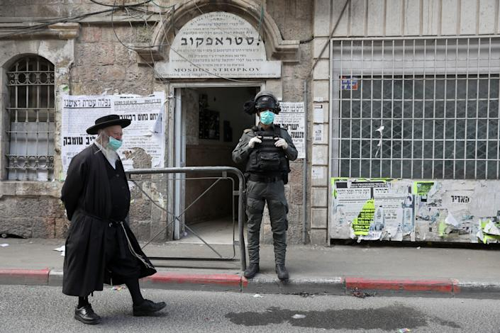 An ultra-Orthodox Jewish man and an Israel Border Police officer in Jerusalem on March 30. (Abir Sultan/EPA-EFE/Shutterstock)