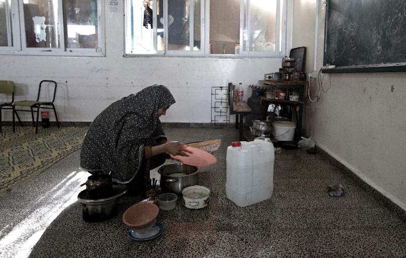 A Palestinian woman cooks at a makeshift kitchen inside a UN-run school in Gaza City on February 25, 2015 (AFP Photo/Mahmud Hams)