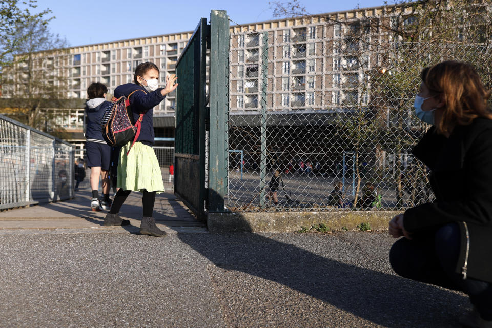 FILE - In this Thursday, April 1, 2021 file photo, Emma Woodroof waves goodbye to her mother Julie as she enters her school in Strasbourg, eastern France. Children, parents and teachers are battling with connection problems across France after an abrupt nationwide switch to online learning saturated networks and embarrassed the government. Paris prosecutors opened an investigation into possible hacking into key systems, the prosecutor's office said Wednesday, April 7. (AP Photo/Jean-Francois Badias)