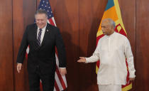 Sri Lankan Foreign Minister Dinesh Gunawardena gestures towards U.S. Secretary of State Mike Pompeo before their meeting in Colombo, Sri Lanka, Wednesday, Oct. 28, 2020. Pompeo plans to press Sri Lanka to push back against Chinese assertiveness, which U.S. officials complain is highlighted by predatory lending and development projects that benefit China more than the presumed recipients. The Chinese Embassy in Sri Lanka denounced Pompeo's visit to the island even before he arrived there, denouncing a senior U.S. official's warning that the country should be wary of Chinese investment. (AP Photo/Eranga Jayawardena, Pool)