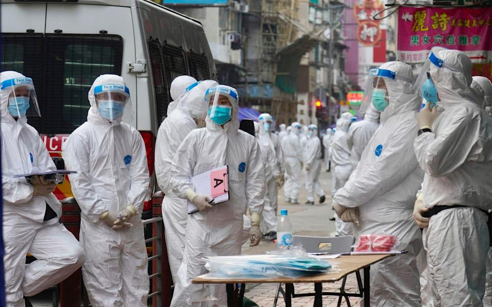 Government investigators wearing protective suits gather in the Yau Ma Tei area in Hong Kong - AP Photo/Vincent Yu