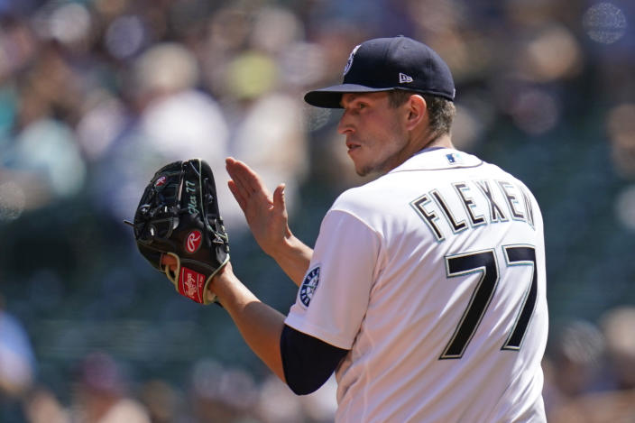 Seattle Mariners starting pitcher Chris Flexen applauds teammates on a third out play against the Texas Rangers to end the top of the second inning of a baseball game Sunday, July 4, 2021, in Seattle. (AP Photo/Elaine Thompson)