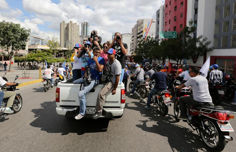 In this Sunday, Dec. 1, 2013 photo, members of the media take photos and video of opposition leader Henrique Capriles during a municipal campaign rally in Caracas, Venezuela. As Capriles campaigned for president of Venezuela last April, he couldn't venture more than a few steps without being hounded by dozens of sharp-elbowed cameramen and photographers. Nearly eight months later, the visibly thinner and exhausted opposition leader is accompanied by just a handful of journalists at what was supposed to be one of the final, electrifying opposition rallies ahead of this weekend's mayoral elections. (AP Photo/Fernando Llano)